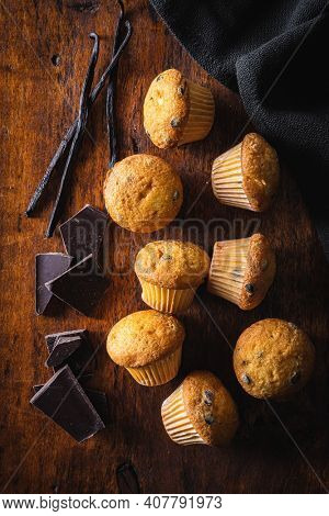 Vanilla muffins. Sweet cupcakes with chocolate and vanilla pods on wooden table. Top view.