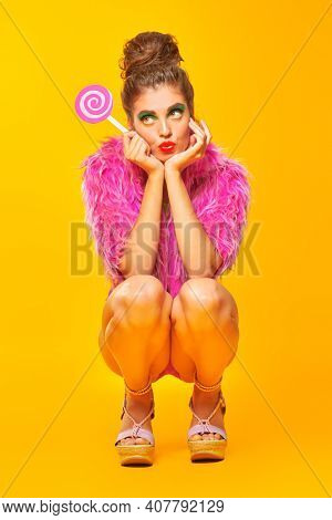 Glamorous fashionable girl posing with paper fuchsia lollipop and in fuchsia fur coat on a bright yellow background. Beauty and cosmetics.