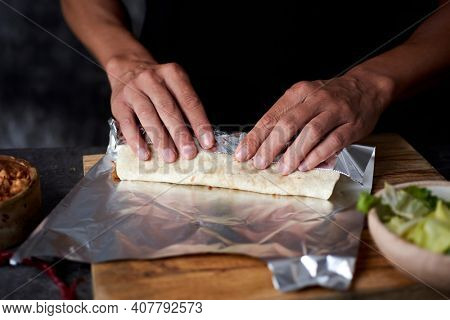 a young man at a table wraps in aluminum foil a durum or a burrito, filled with chicken meat cooked with different vegetables such as onion or red and green pepper