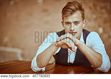 Handsome young man sitting at a table in a caf