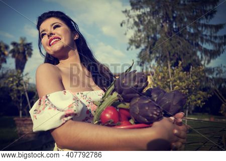 woman in white dress harvesting some fresh red cherry tomatoes in her own garden. concept of organic, ecological and biological farming and sustainability,green planet,connection with nature.