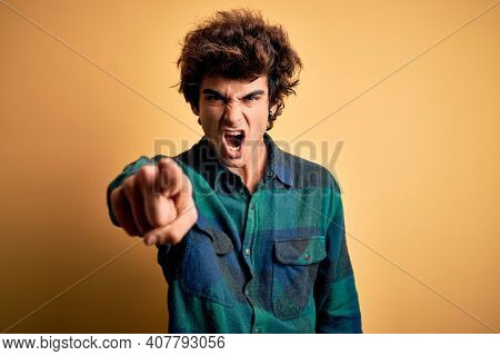 Young handsome man wearing casual shirt standing over isolated yellow background pointing displeased and frustrated to the camera, angry and furious with you