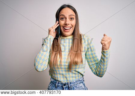 Young blonde woman having a conversation talking on smartphone over isolated background screaming proud and celebrating victory and success very excited, cheering emotion