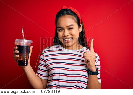 Young asian girl drinking cola fizzy refreshment using straw over isolated red background surprised with an idea or question pointing finger with happy face, number one
