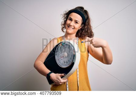 Young beautiful woman with curly hair holding weighing machine and tape measure very happy pointing with hand and finger