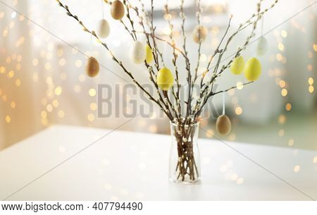 holidays and object concept - pussy willow branches decorated by easter eggs in vase on table over bokeh lighs