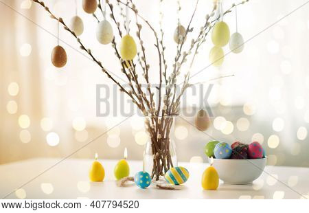 holidays and object concept - pussy willow branches decorated by easter eggs in vase and candles on table over bokeh lighs