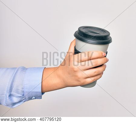 Hand of caucasian young woman holding cup of takeaway coffee over isolated white background