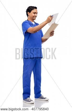 healthcare, profession and medicine concept - happy smiling indian doctor or male nurse in blue uniform writing medical report on clipboard over white background