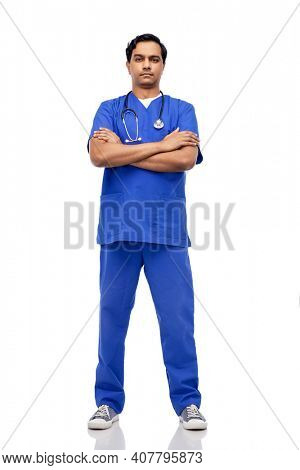 healthcare, profession and medicine concept - indian doctor or male nurse in blue uniform with stethoscope and crossed arms over white background