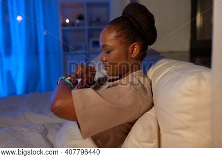 people, bedtime and rest concept - african american woman looking at health tracker in bed at home at night