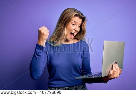Young beautiful blonde woman working using laptop over isolated purple background screaming proud and celebrating victory and success very excited, cheering emotion