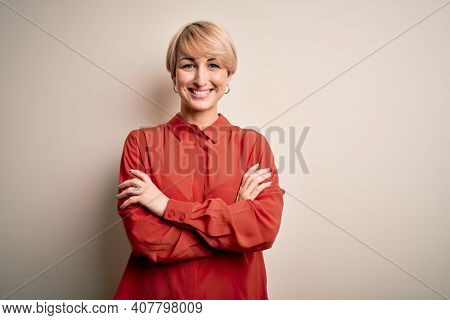 Young beautiful business blonde woman with short hair standing over isolated background happy face smiling with crossed arms looking at the camera. Positive person.