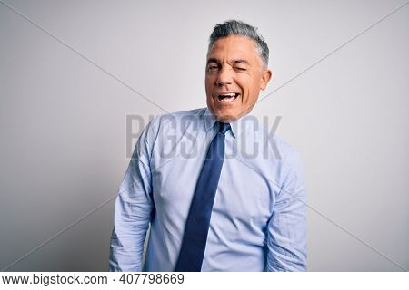 Middle age handsome grey-haired business man wearing elegant shirt and tie winking looking at the camera with sexy expression, cheerful and happy face.