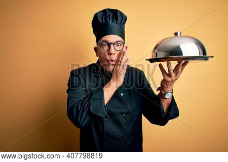 Middle age handsome grey-haired waiter man wearing cooker uniform and hat holding tray hand on mouth telling secret rumor, whispering malicious talk conversation