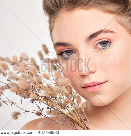Beautiful young  woman with healthy skin face. Skin care concept. Closeup female face with a freckled. Women's face with field  flowers. Teen girl with a clean skin of face, isolated.