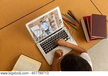 Overhead view of male student having a video call with male teacher on laptop at school. distance learning online education concept