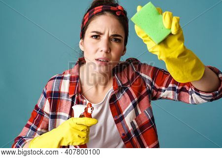Perplexed caucasian young woman in gloves cleaning glass isolated over blue background