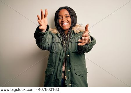 Young african american woman wearing winter parka coat over isolated background looking at the camera smiling with open arms for hug. Cheerful expression embracing happiness.