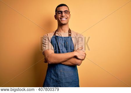 Young handsome african american shopkeeper man wearing apron over yellow background happy face smiling with crossed arms looking at the camera. Positive person.