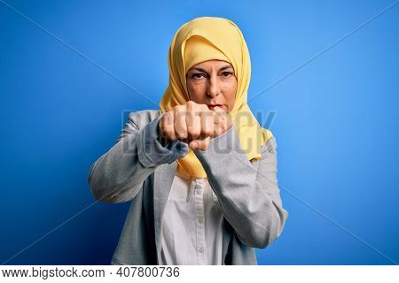 Middle age brunette business woman wearing muslim traditional hijab over blue background Punching fist to fight, aggressive and angry attack, threat and violence