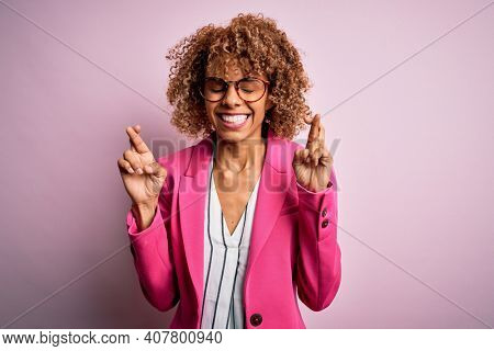 Young african american businesswoman wearing glasses standing over pink background gesturing finger crossed smiling with hope and eyes closed. Luck and superstitious concept.