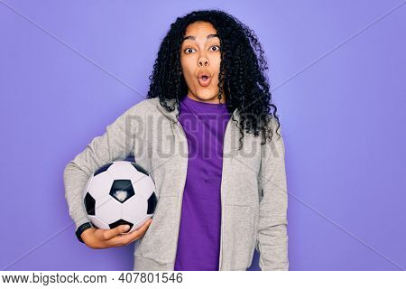 African american curly player woman playing soccer holding football bal over purple background scared in shock with a surprise face, afraid and excited with fear expression