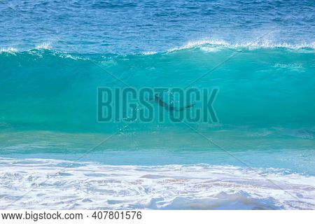 turquoise wave with people silhouette at Sandy Beach, Oahu, Hawaii USA