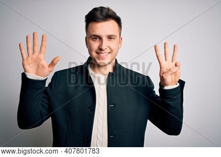 Young handsome business mas wearing elegant winter coat standing over isolated background showing and pointing up with fingers number eight while smiling confident and happy.