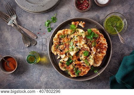cauliflower steaks with herb sauce and spice. plant based meat substitute