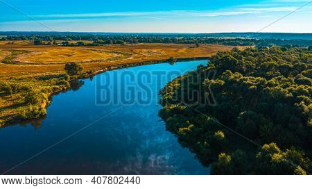 Aerial  view of a beautiful summer  landscape over river while dawn. Top view over river with a smooth water surface reflecting blue sky.