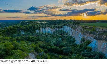 Aerial drone view - Beautiful summer landscape old chalk quarry while sunset. Bird view over nature landscape with old chalk quarry. Beautiful hilly.
