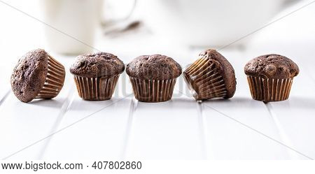 Chocolate muffins. Sweet dark cupcakes on white table.