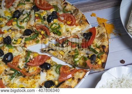 Vegetable Pizza Cut With A Wedge Shot From Above Isolated On A Wooden Table