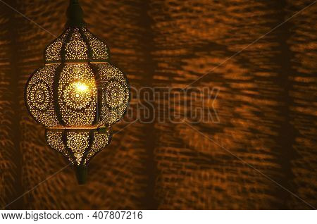 Moroccan Golden Lamp With Circular Patterns Of Light On Wall For Bohemian Theme.