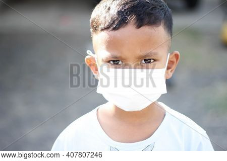 Asia Boy Wearing Facial Mask For Protect Corona Virus And Air Pollution Pm2.5 With Blurred Backgroun