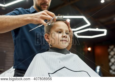 Little Client In Barbershop. Cute Boy Sitting In Armchair In The Barbershop While Male Barber With S
