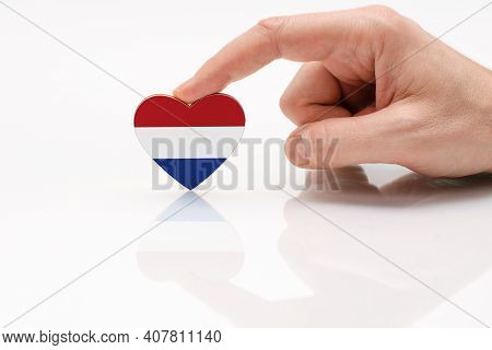Love And Respect Netherlands. A Man's Hand Holds A Heart In The Shape Of The Netherlands Flag On A W