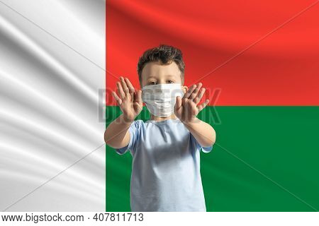 Little White Boy In A Protective Mask On The Background Of The Flag Of Madagascar. Makes A Stop Sign