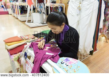Nha Trang, Vietnam - March 29, 2018: A Young Vietnamese Embroiderer Working On A Silk Embroidery. Em