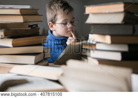 Five Year Old Boy In Glasses Reading A Book With A Stack Of Books Next To Him. Smart Intelligent Pre