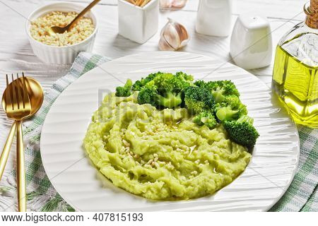 Broccoli Potato Mash Sprinkled With Chopped Almonds Served With Steamed Broccoli Florets On A Plate