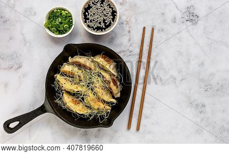 Asian Vegetarian Dumplings Gyozas Potstickers Fried On Cast-iron Pan, Served With Chopsticks And Bow