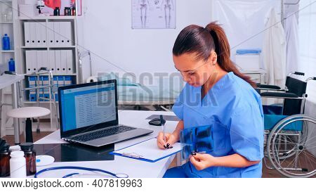 Nurse Checking X-ray Result, Reading Patients List, Taking Notes In Clipboard Holding Radiography. M