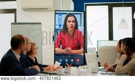 Diverse Executive Team Meeting At Conference Video Call Looking At Huge Display. Business People Tal