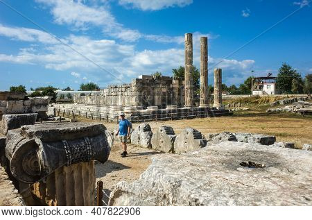 Western tourist standing among the ruins columns of Temple of Leto in Letoon Ancient City in village Kumluova, Turkey. Sunny day, Greek culture temple ruins
