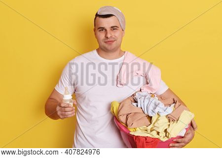 Man Doing Laundry At Home And Looking After Newborn, Holding Feeding Bottle And Basin With Linen, Lo