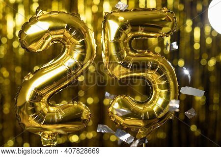 Golden Number 25 Twenty Five Made From An Inflatable Balloon, On A Yellow Background. One Of The Com