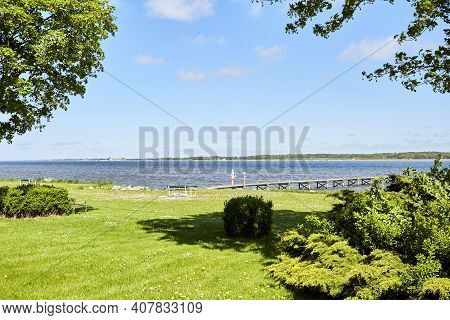 Green Field By The Water On Hot Summer Day