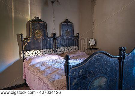 November 2020, Italy. Antique Wrought Iron Bed In A Bedroom Of An Abandoned House In Northern Italy.